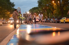 """Mat Tomezsko and volunteers install Tomezsko's mural """"14 Movements: A Symphony in Color and Words"""" along Broad Street's median during July. 