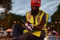 """Volunteer Johnny Jones helps install the mural """"14 Movements: A Symphony in Color and Words"""" on the median of Broad Street during July. 