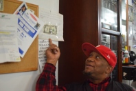 A tattered one dollar bill hangs behind Darryl Salley's desk at 1617 Barber Shop & Beauty Salon on Cecil B. Moore Avenue. It symbolizes the importance of building relationships over making money for the shop. | THE TEMPLE NEWS