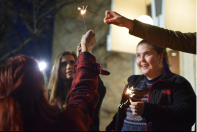 Temple student Jill Caldwell smiles as she looks at one of her peers holding up a sparkler at protest the night before President Donald Trump's inauguration. | THE TEMPLE NEWS